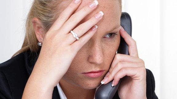 Eine Frau hält einen Telefonhörer in der Hand