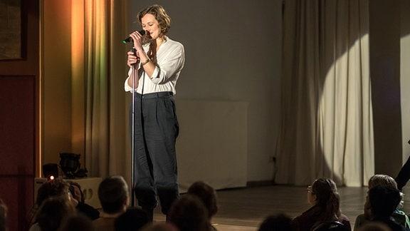 Josefine Berkholz auf der Bühne vor dem Mikro.