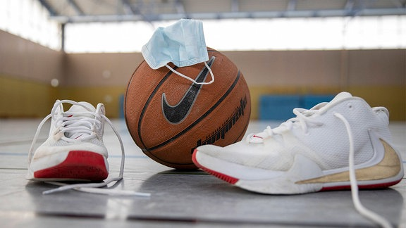 Sportschuhe, Basketball und eine Mund-Nasenmaske.