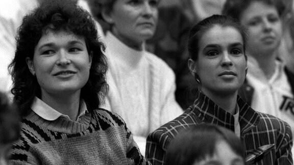 Katarina Witt (re.) und Anett Pötzsch (beide DDR) auf der Tribüne, 1988