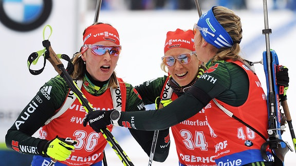 Denise Herrmann, Karolin Horchler und Franziska Preuß (v.l.) jubeln gemeinsam im Ziel.