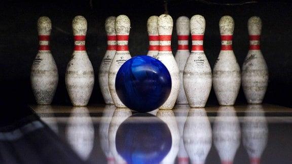 Bowlingball rollt auf die Pins zu.