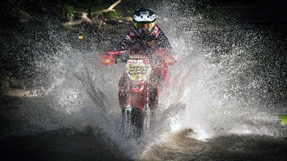 Motocrossfahrer fährt durchs Wasser.
