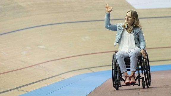 Im Velodrom in Berlin winkt Kristina Vogel in die Runde.