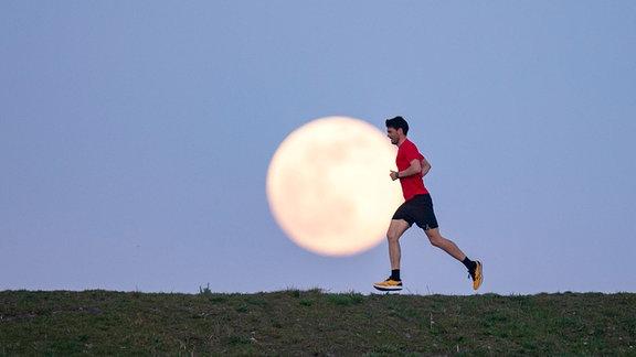 Laufender Mann vor Vollmond