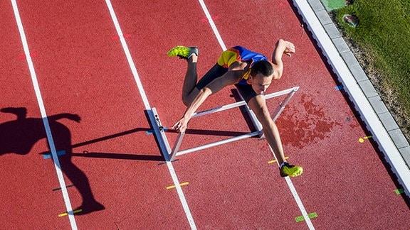 Ein Läufer springt über eine Hürde