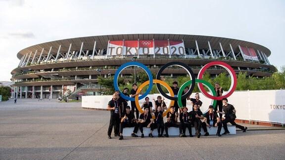 Eine Gruppe Posiert vor dem Olympiastadion in Tokyo.