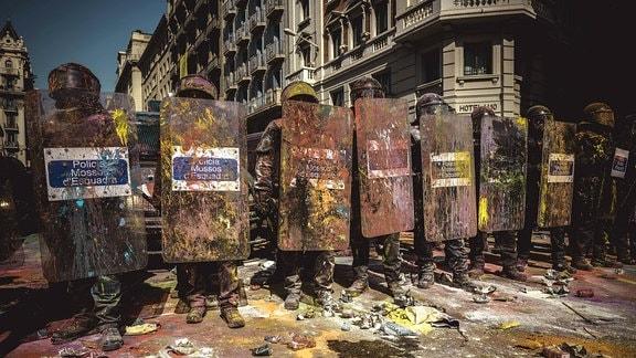 Polizisten der katalanischen Regionalpolizei Mossos d'Esquadra wird in Barcelona mit Farbbeuteln beworfen