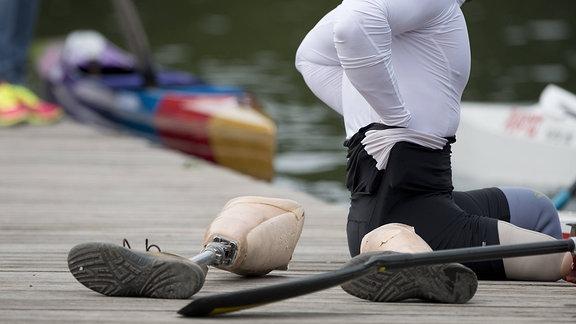 ein Parakanute hat seine Prothesen auf dem Steg abgelegt und steigt in sein Kanu ein,