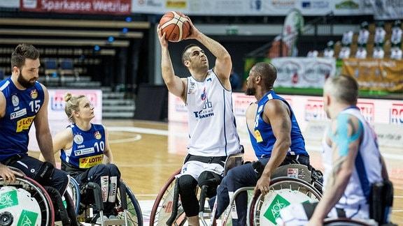 Rollstuhlbasketballspieler wirft den Ball.