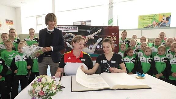 Trainerin Gabriele Frehse und Pauline Schäfer trägt sich in Anwesenheit von OB Barbara Ludwig in das Goldene Buch der Stadt Chemnitz ein.