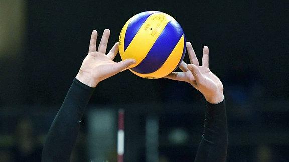 Symbolbild Volleyball. Ein Volleyball wird mit zwei Händen hoch gehalten.