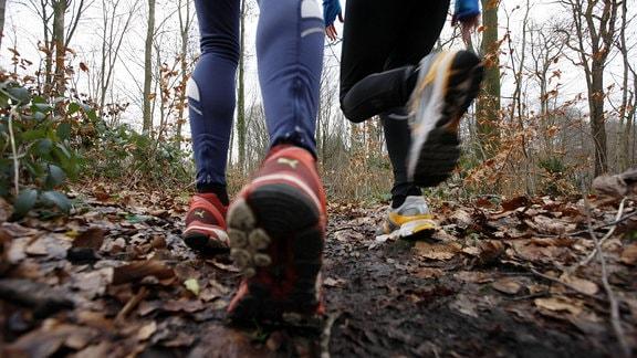 Zwei junge Frauen laufen im Winter im Wald.
