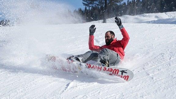 Ein Snowboarder fällt hin.