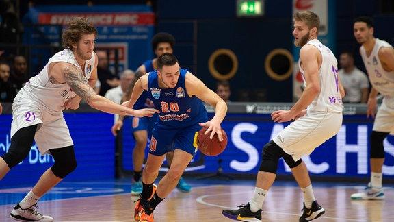 Drei Basketballer während des Spiels.