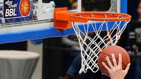 Ein Ball neben einem Basketballkorb wird von einer Hand gehalten.