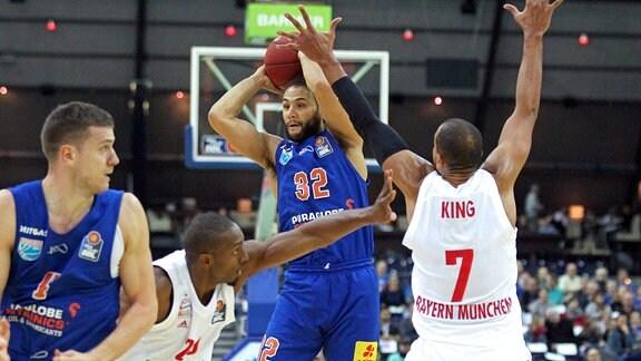Basketballspieler wirft Ball, Gegenspieler versuchen ihn daran zu hindern.