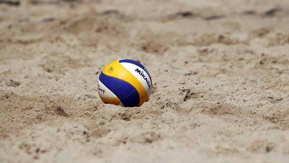 Ein Volleyball liegt im Sand.