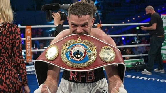 Roman Fress jubelt mit WBO Gürtel im Ring.