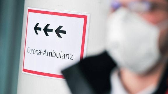 Person mit Mundschutz neben Hinweisschild Corona-Ambulanz
