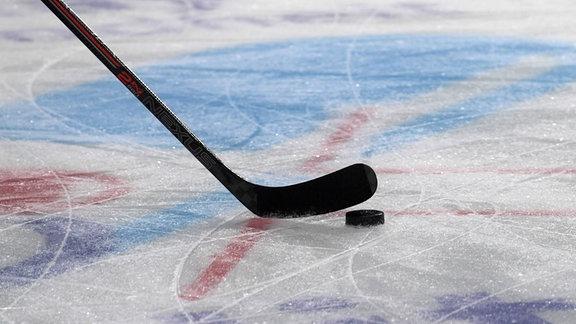 Puck und Schläger auf dem Eis