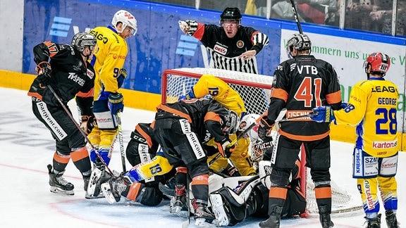 Das Tor ist voll. Spieler im, am und vor dem Eishockeytor, dahinter der Schiedsrichter.