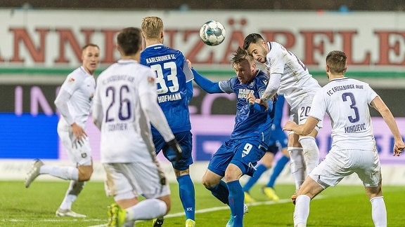Spieler von Karlsruher SC gegen FC Erzgebirge Aue im Zweikampf.