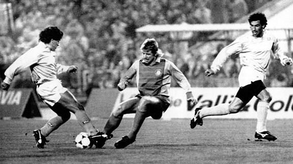 Der Leipziger Lok-Abwehrspieler Matthias Lindner (2.v.l.) attackiert den ballführenden argentinischen Neapel-Star Diego Maradona (l). Rechts wartet Neapels mitlaufender brasilianischer Stürmer Careca auf den Ball.