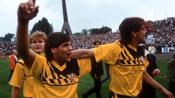Ulf Kirsten und Ralf Minge Arm in Arm während der Meisterfeier 1989, Ralf Hauptmann folgt ihnen