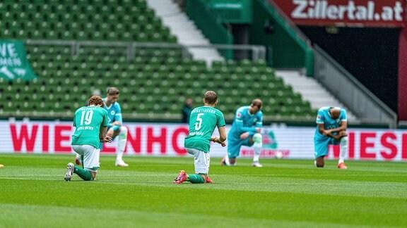 Vor dem Spiel gegen den VFL Wolfsburg knien die Spieler am Mittelkreis.