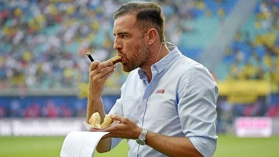 Christoph Metzelder steht Bratwurst essend am Spielfeldrand.