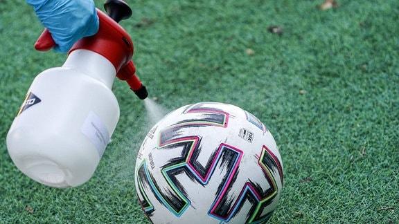 Ein Ball der Marke adidas Uniforia wird mit Desinfektionsmittel eingesprüht.