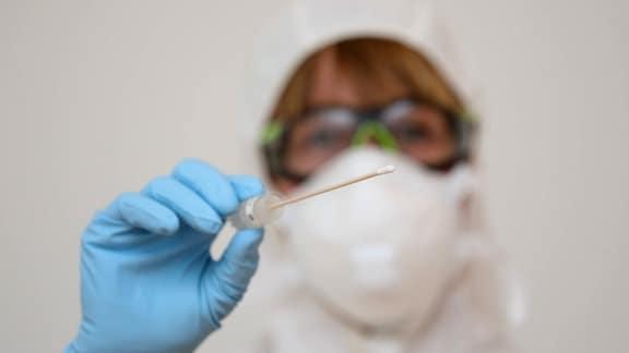 Eine Ärztin hält das Wattestäbchen eines Coronavirus-Tests in der Hand