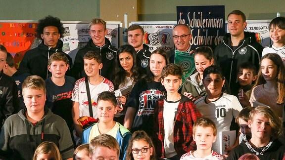 Leroy Sane (19,GER), Julian Brandt (10,GER), Timo Werner (9,GER) und Torhüter Manuel Neuer (1,Deutschland) mit Schülern der 94. Oberschule