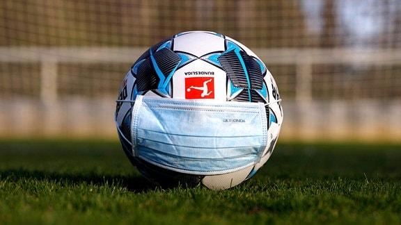Bundesligafußball mit aufgesetzter Mundschutzmaske