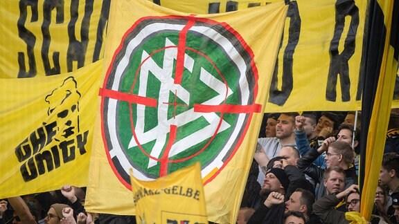 Dortrmunder Fans halten einen Banner mit DFB Logo und Fadenkreuz hoch