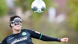 Elias Abouchabaka mit Schutzmaske im Gesicht beim Anvisieren des Balls.