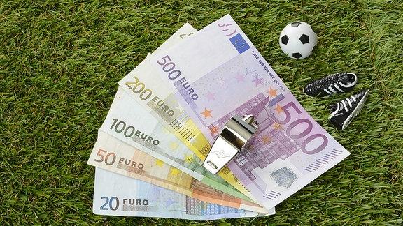 Symbolbild: Euroscheine, Trillerpfeife und Fußball liegt auf dem grünen Rasen.