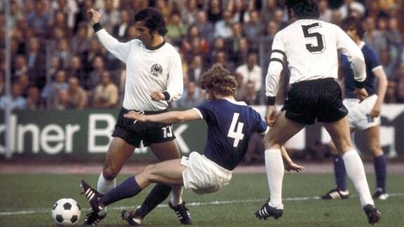 Konrad Weise (Mitte, DDR) attackiert Gerd Müller (li.), Franz Beckenbauer (beide BR Deutschland) schaut zu