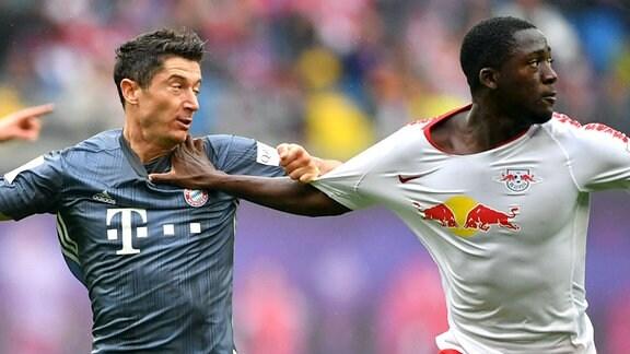 Robert Lewandowski (FC Bayern), und Ibrahima Konate (RB Leipzig), halten sich gegenseitig, hinten Willy Orban (RB Leipzig).