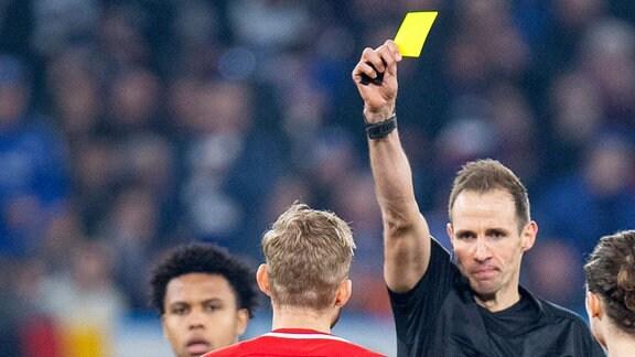Schiedsrichter Sascha Stegemann, gibt Konrad Laimer, RB Leipzig, die gelbe Karte,