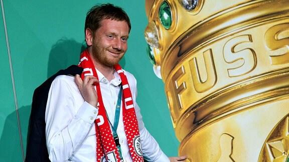 Michael Kretschmer vor einem Plakat mit dem DFB-Pokal