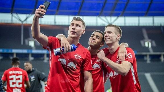 Willi Orban jubelt nach dem Spiel mit Tyler Adams und Dani Olmo und macht ein Selfie mit dem Handy.