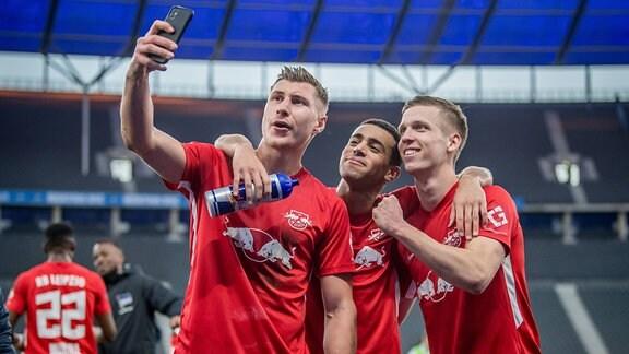 Leipzigs Willi Orban jubelt nach dem Spiel mit Tyler Adams und Dani Olmo und macht ein Selfie mit dem Handy