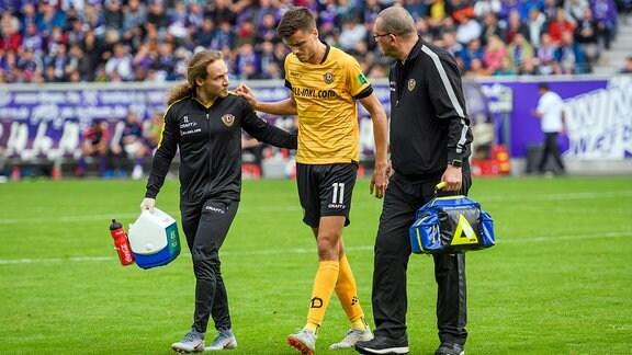 Dresdens Alexander Jeremejeff wird von Physiotherapeut Tobias Lange links und Mannschaftsarzt Falko Moritz begleitet