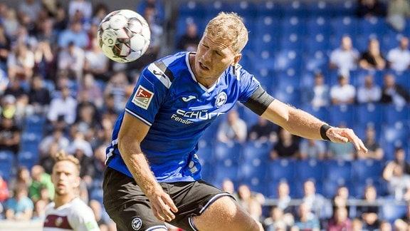 Arminia Bielefeld - Dynamo Dresden. Bielefelds Fabian Klos spielt einen Kopfball.