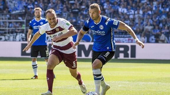 Arminia Bielefeld - Dynamo Dresden. Dresdens Rico Benatelli (l.) und Bielefelds Florian Hartherz kämpfen um den Ball.