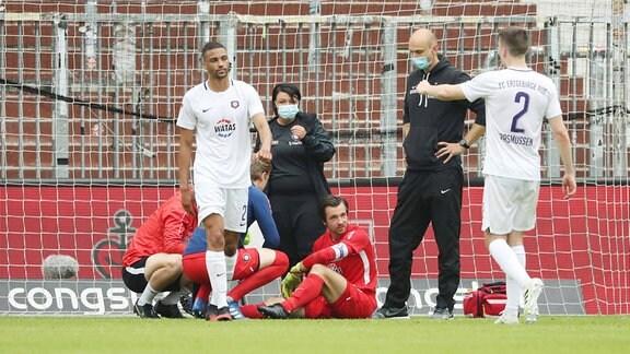 Torhüter Martin Männel (1, Aue) muss wegen einer Schulterverletzung von Physiotherapeutin Marie Koch (Aue) und Teamarzt Stephan Rezmann behandelt werden.