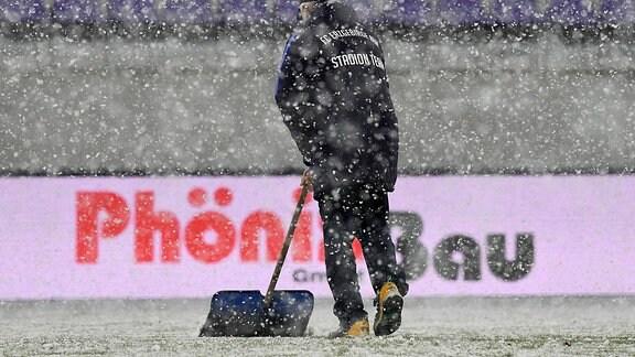 Ein Helfer raeumt Schnee vom Platz.