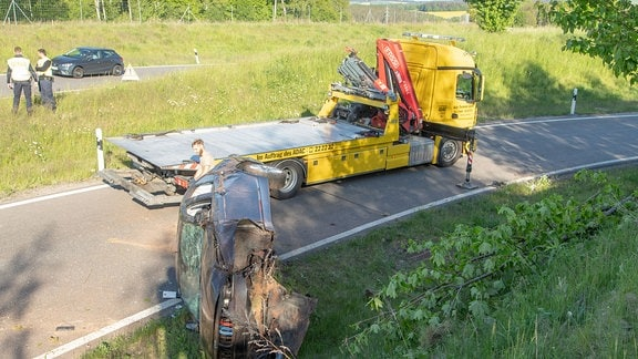 Unfallwrack liegt auf der Seite am Straßenrand, dahinter ein Abschlepplastkraftwagen.